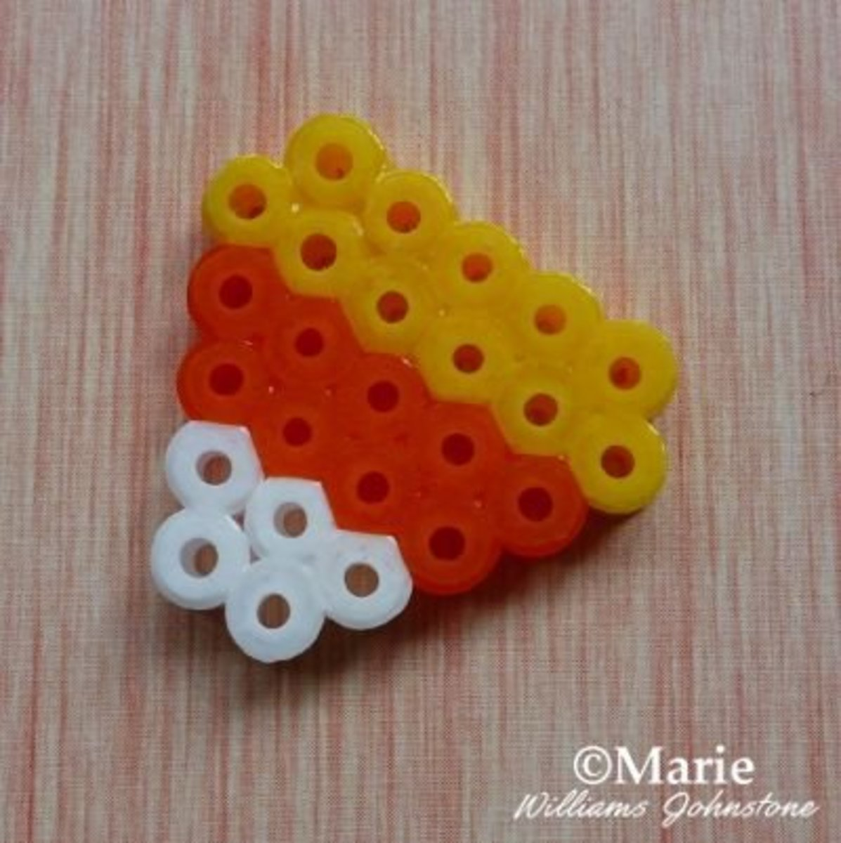 Make some tiny candy corn designs with fused perler beads for Halloween and turn them into charms, necklaces or even little earrings to wear.
