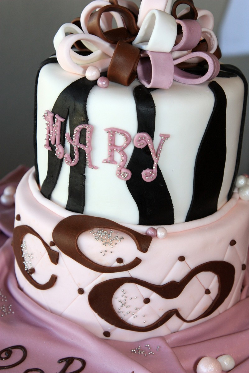 A cake in a striking black, white, brown, and pink theme.