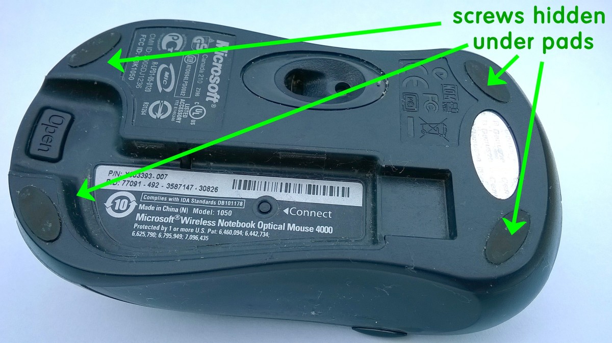 The screws holding this Microsoft optical mouse together, are hidden under pads