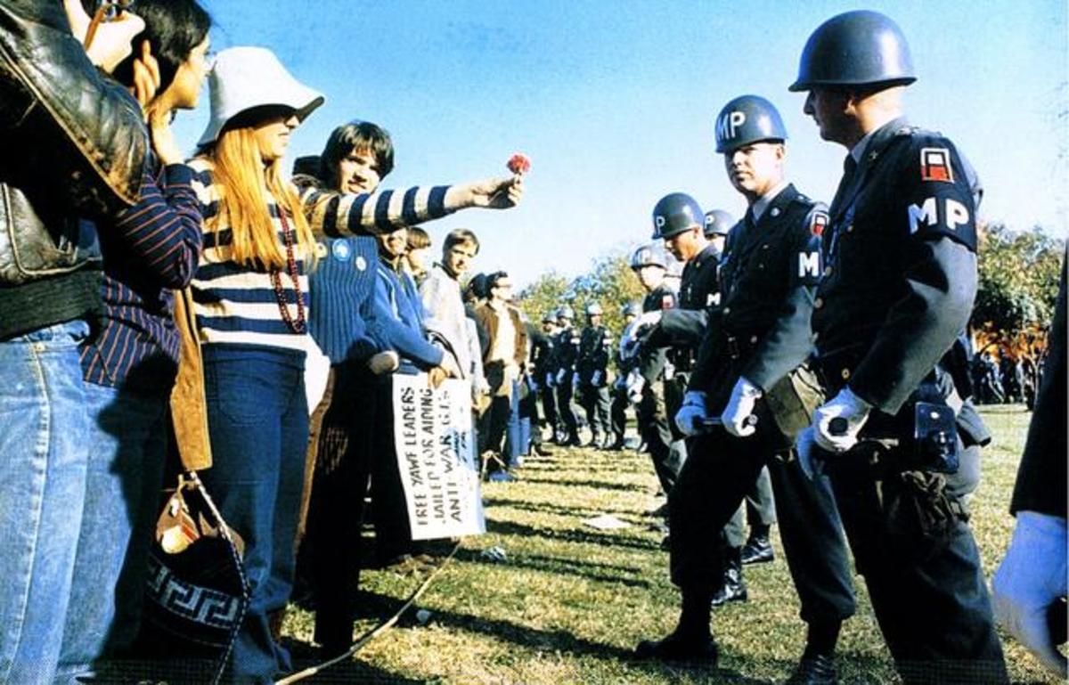 Activist offering a flower to a military police officer: Make love, not war.