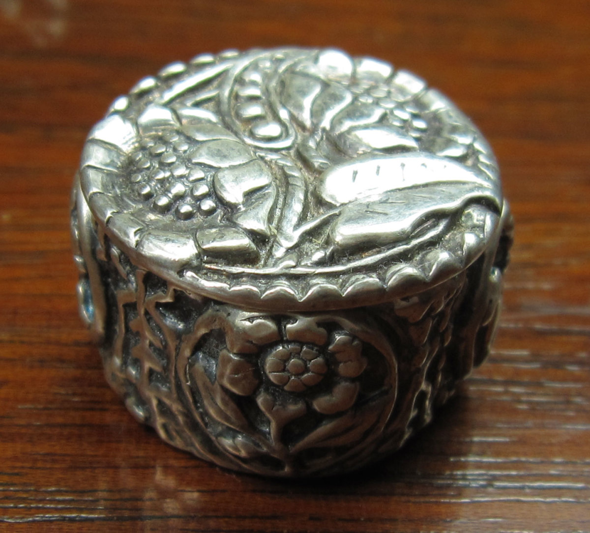 "Round fine silver lidded box (approx. 1¼"" diameter). Top of lid and four textured appliqués around sides made from my own molds of vintage & antique buttons."