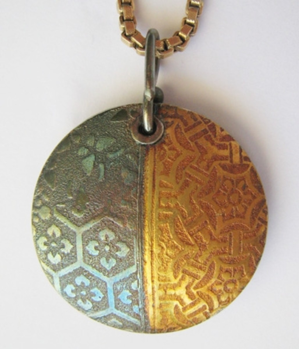 Back of fine silver PMC lentil pendant with 24k gold keum-boo, textured with two tear-away textures taped side-by-side.