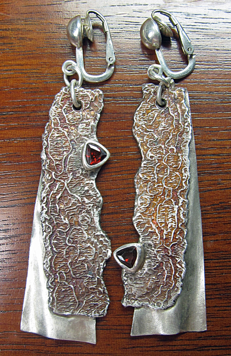 Asymmetrical silver clay earrings textured with molded lace. Designed by Margaret Schindel.