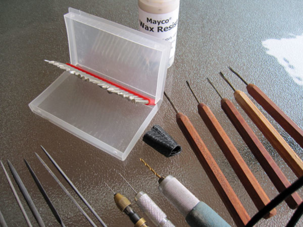 Dockyard micro carving tools, hand drills, diamond burs, needle files, metal-reinforced leather thimble for carving metal clay and Mayco wax resist for water etching.  Photo: Margaret Schindel