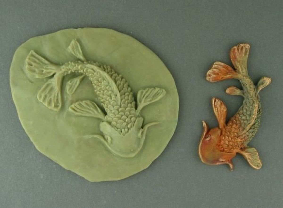 Bronze Koi with the mold in which it was formed; you can see the clay shrinkage in the difference in size between the mold and the fired piece.
