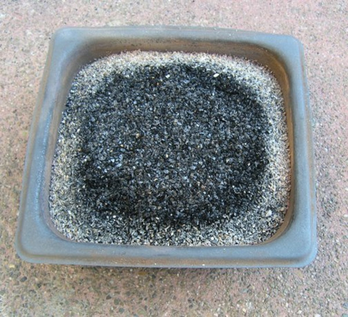 Stainless steel firing pan with ash topped activated carbon after firing