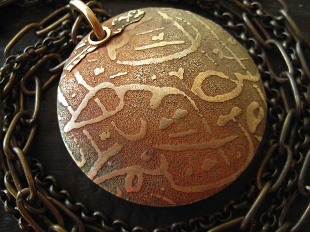 Bronze lentil pendant with tear-away textures