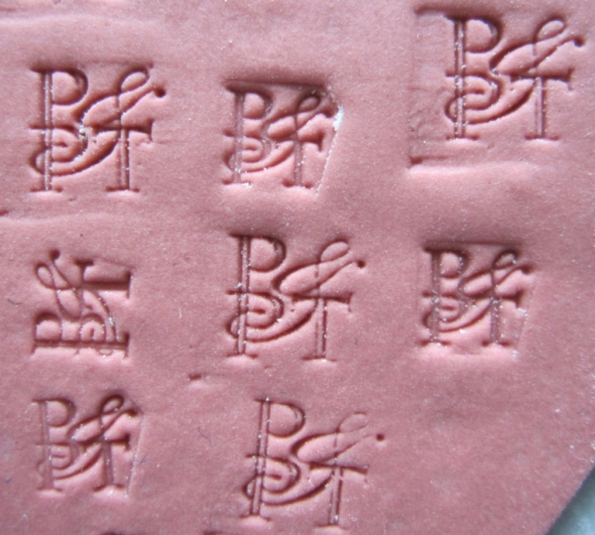 Test impressions of a customized logo stamp on a sheet of clay