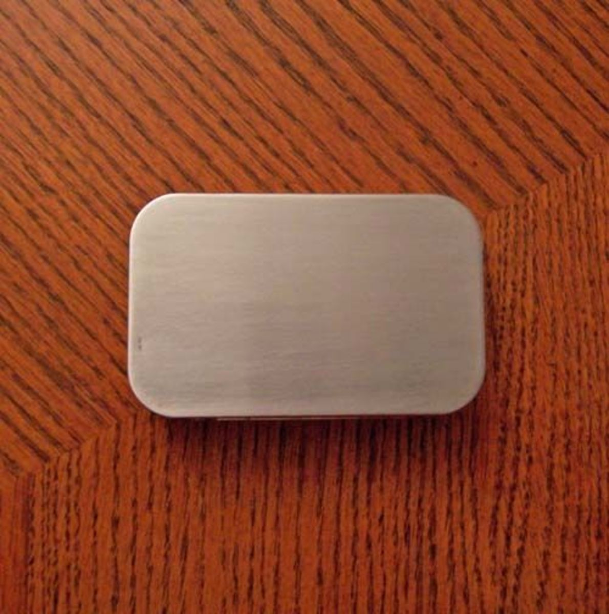 An Altoids tin with its paint removed and its surface sanded smooth