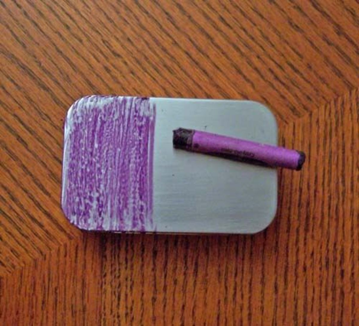 A blank tin getting a coat of purple wax crayon
