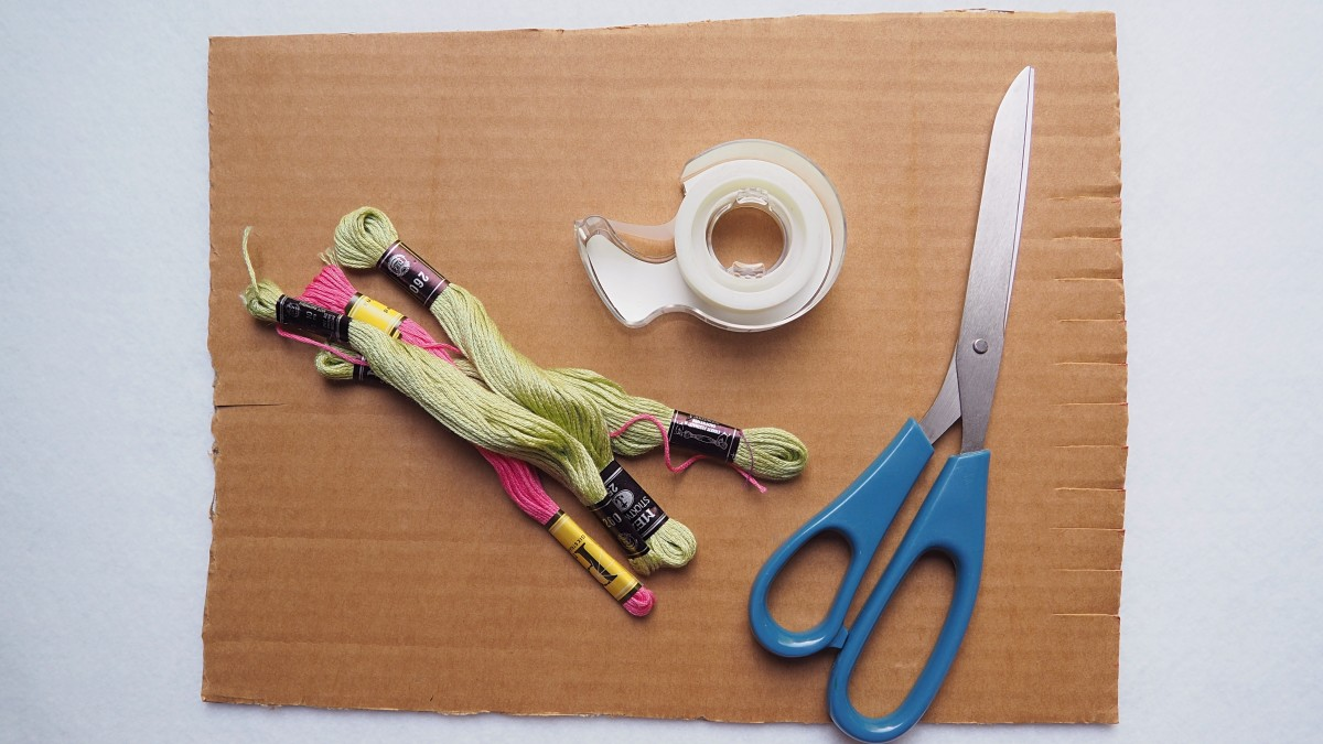 You'll need embroidery thread, scissors, tape, and cardboard (to make a loom).
