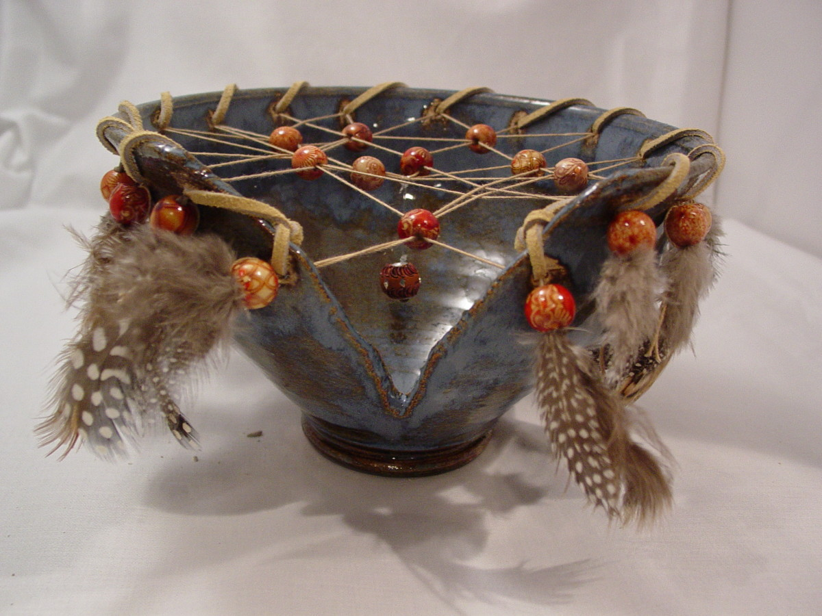 bowl form with decoration of leather, beads and feathers