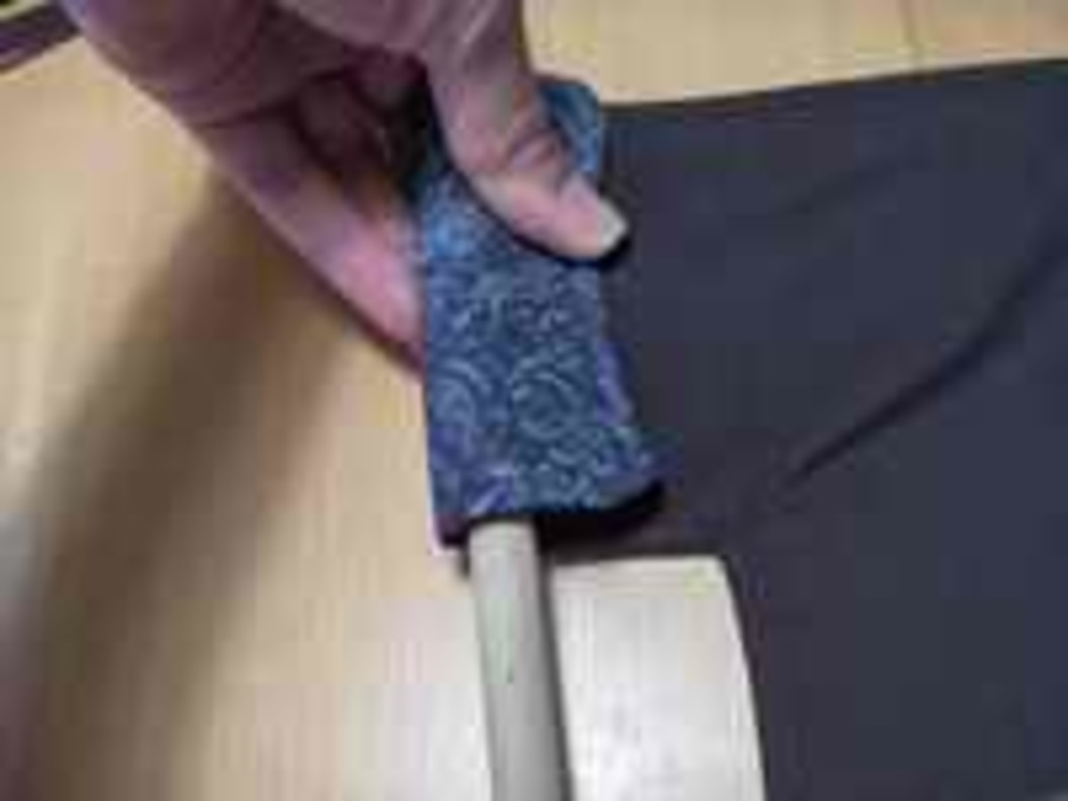 Make sure the fabric fits around the dowel. Then, pin the fabric at the right spot and slide the handle back out.