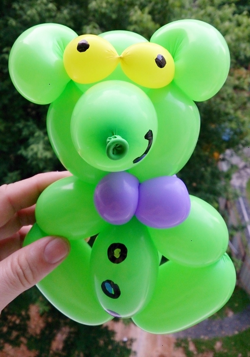 The creation of a green teddy bear with a purple bow tie is a lighthearted way to use balloons.