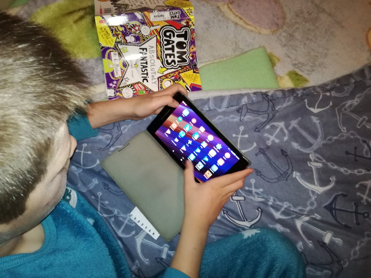 My boy using his tablet, displaying how easy it is for a child to handle a 8 inch tablet.