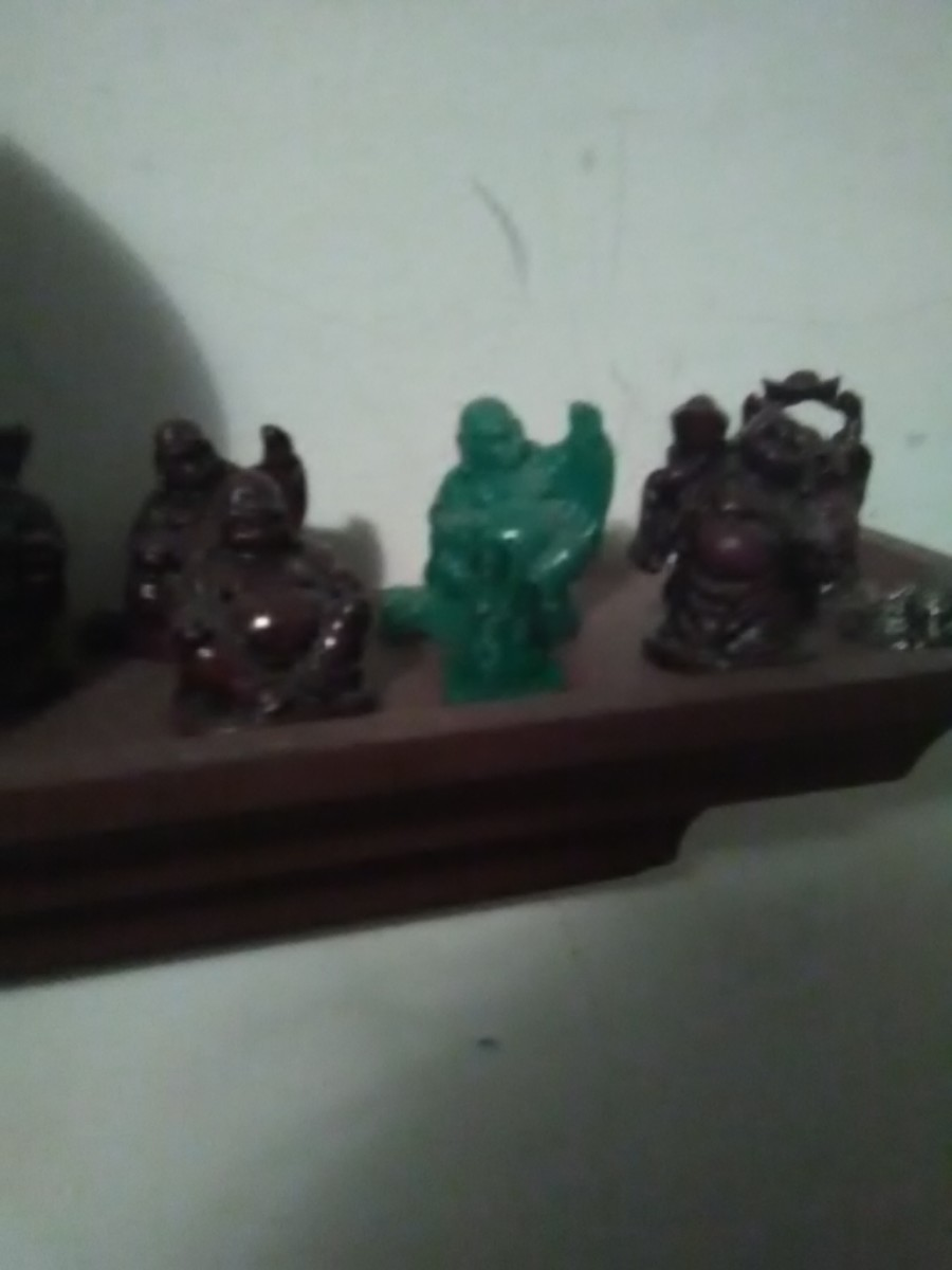 3D printed model is the small green plastic statue in front of the jade (green) laughing Buddha. In Cura, 3D objects can be scaled for different sizes and slightly different shapes.