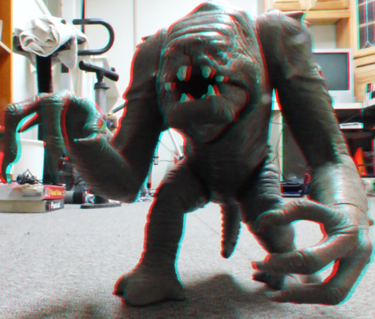 3D photo of a Rancor Star Wars toy with its hands coming out of the screen.