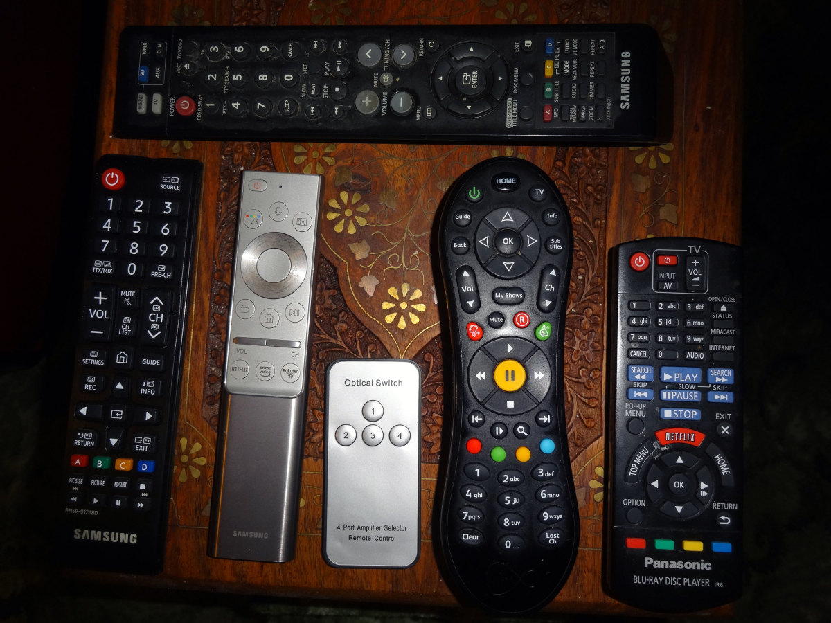 The top remote is for the sound system. The remotes below, from left to right, are TV, universal remote, optical audio switch, cable TV, and Blu-ray player.