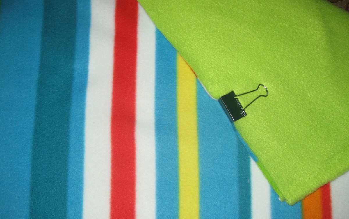 After choosing two types of fleece and cutting them into equal pieces, clip two layers together with a paper clip.