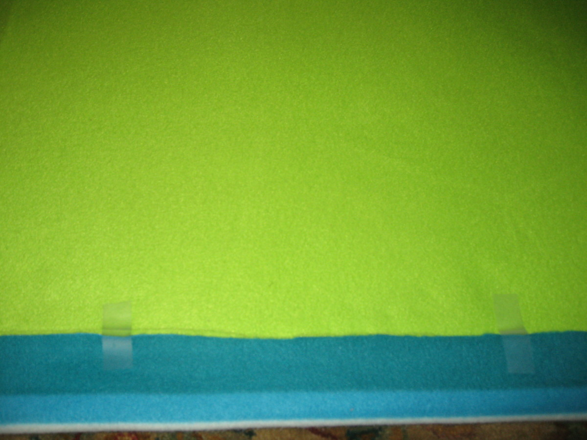 Fold the fabrics up about an inch and a half and tape along one side. Cut until you reach the top (solid green).