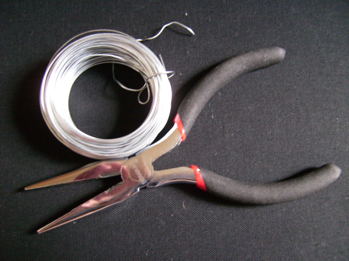 A roll of wire and needle nose pliers from a hardware store