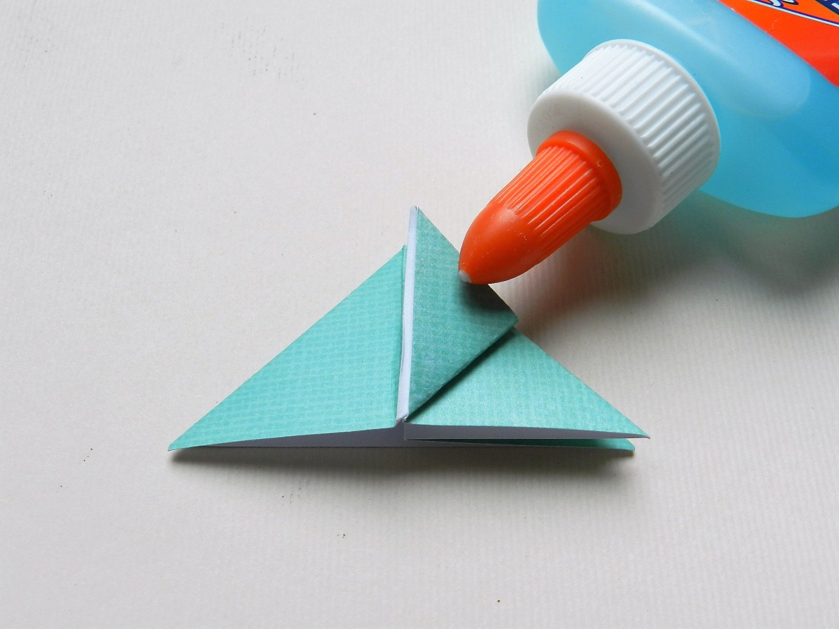Fold the left tip up to the top of the triangle.