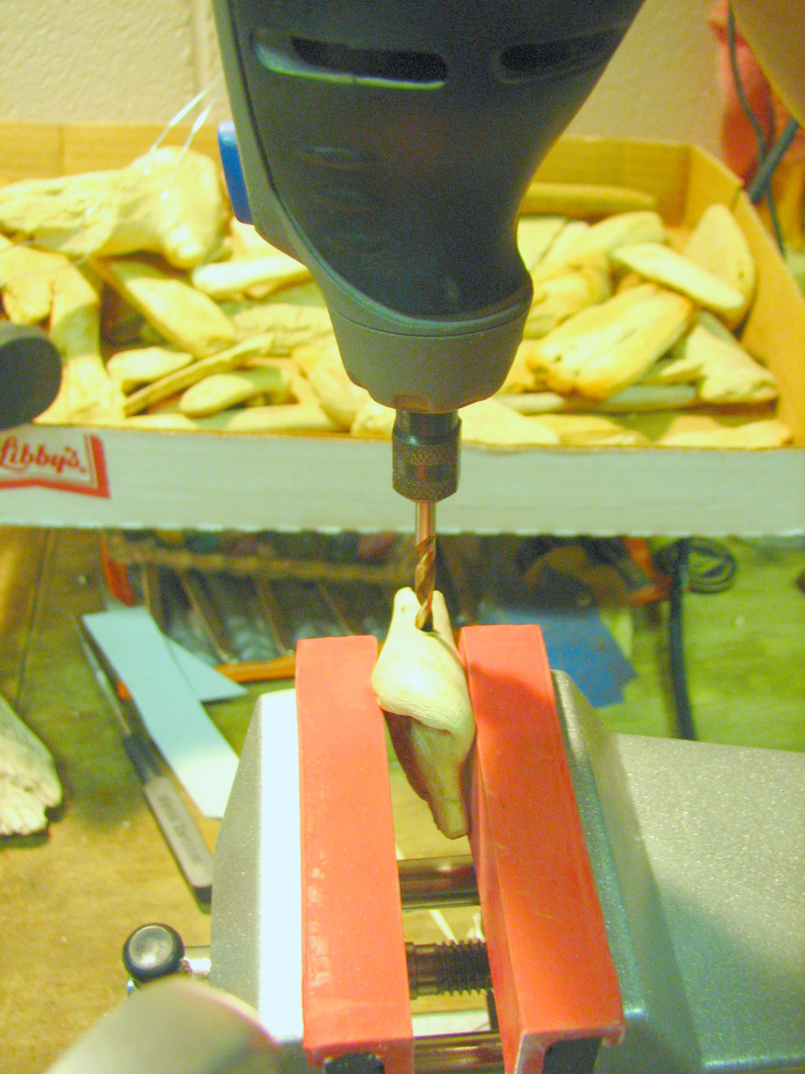 Clamp the selected driftwood in a vise or hold it with a pair of pliers when drilling with the rotary tool