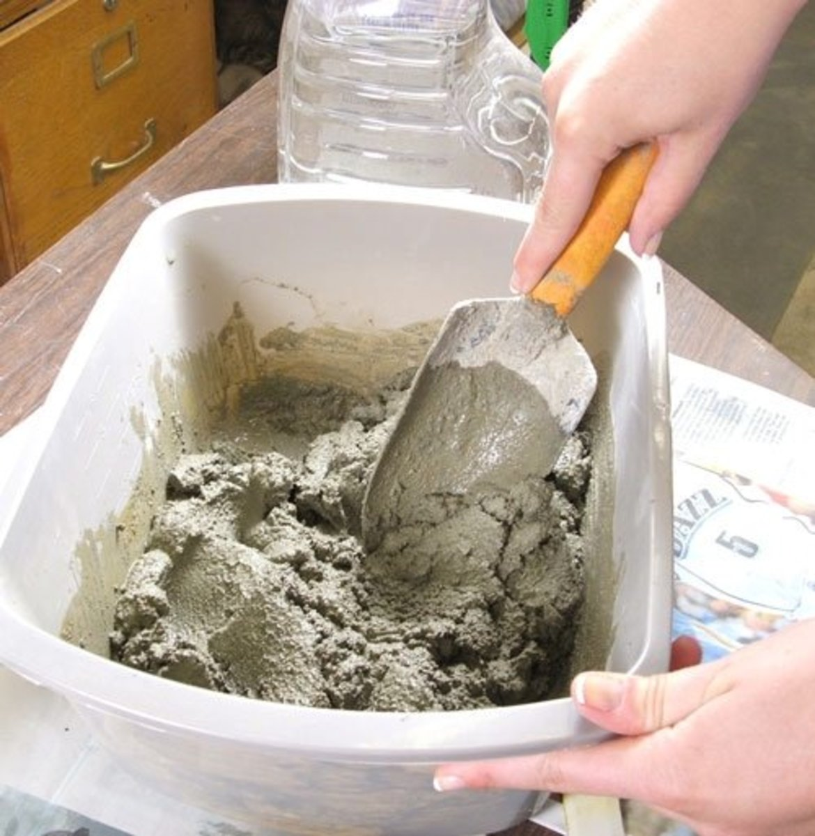 Step 5. Using a trowel, thoroughly mix the dry mortar with the water until it is like peanut butter. If the mix is too dry add a small amount of water until it is of the desired consistency.  If is too runny add  dry mortar.