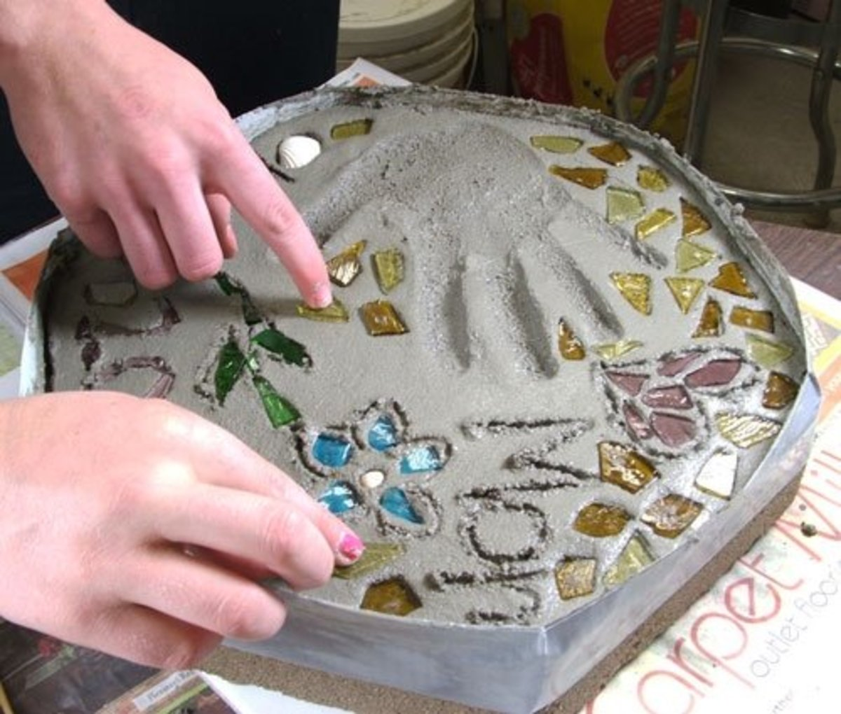 Step 7. Using a pencil or thin stick, carve any letters/numbers into the mortar. Transfer your glass and other decorative items to the wet mortar gently pressing each piece into the wet cement.  Allow the mortar to dry (set-up) for about 15 to 20 min