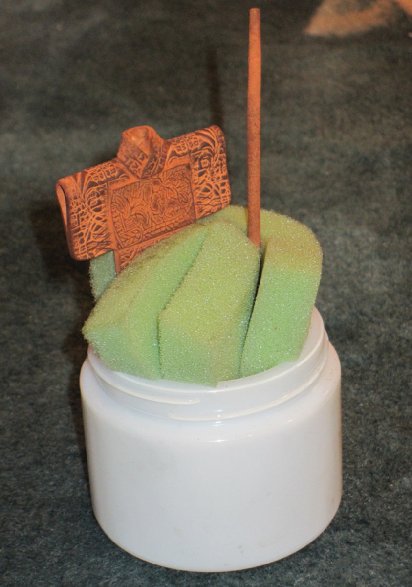Copper clay pieces propped up vertically in a folded piece of foam sheet, using gravity to advantage while fresh clay additions or repaired breaks are drying.