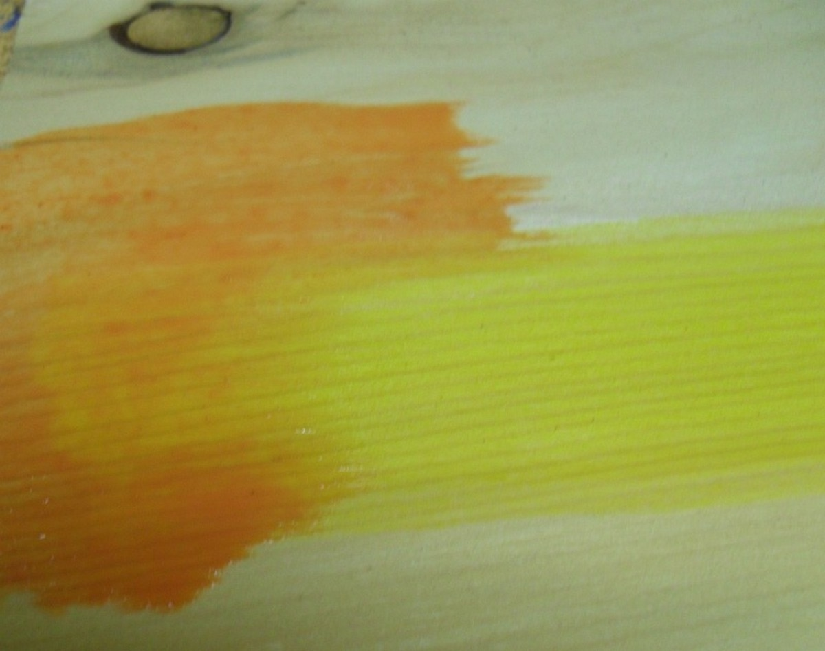 Creating an orange stain by mixing on the wood.