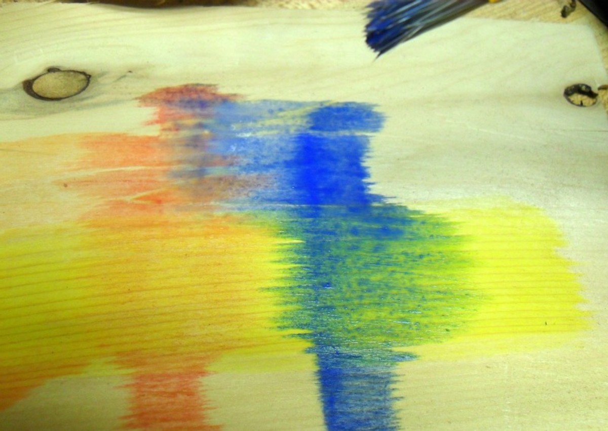 Creating orange and green stains by mixing on the wood.