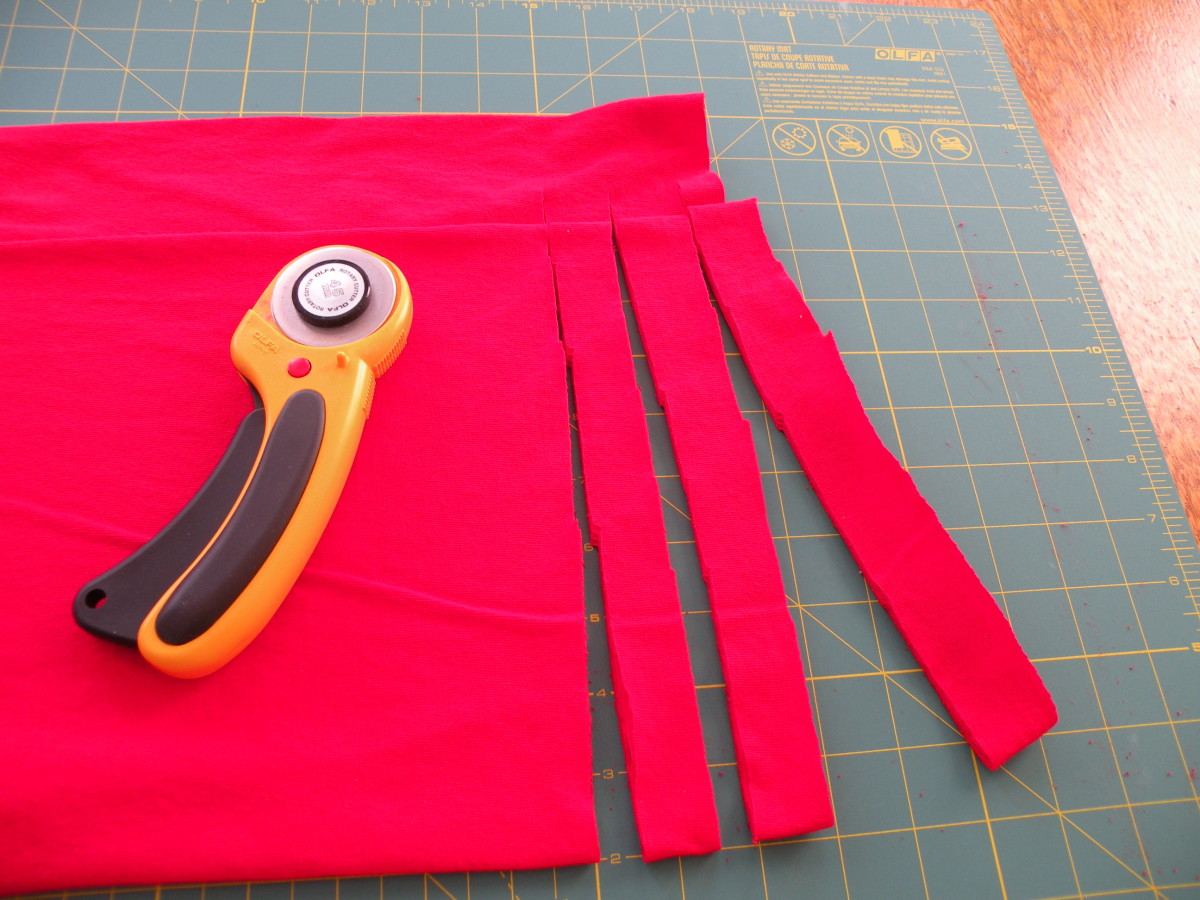 Begin to cut 3/4 inch slits in the fabric, but stop short of cutting the strips completely off the shirt.