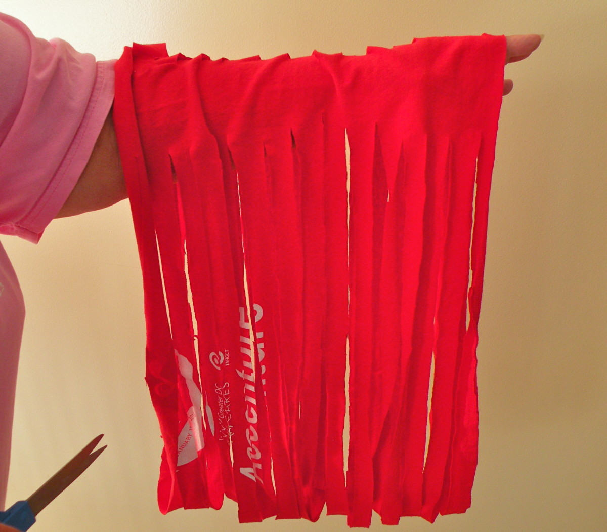 When the T shirt is cut into strips, slide your hand into the tube to separate it.