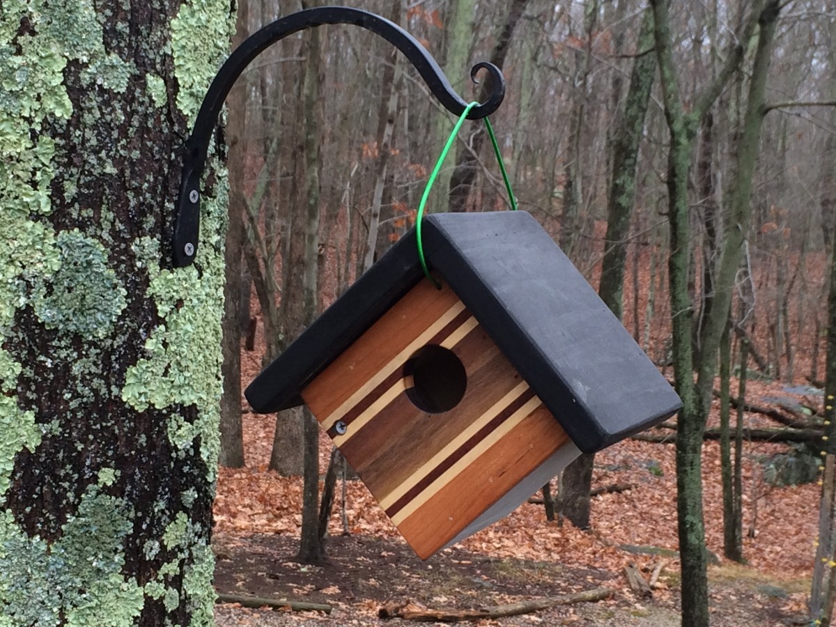 The front of this small hanging birdhouse was made by gluing together strips of different hardwoods including teak, mahogany, walnut and maple.