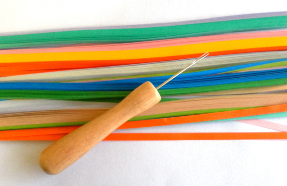Strips of colourful quilling paper and quilling tool