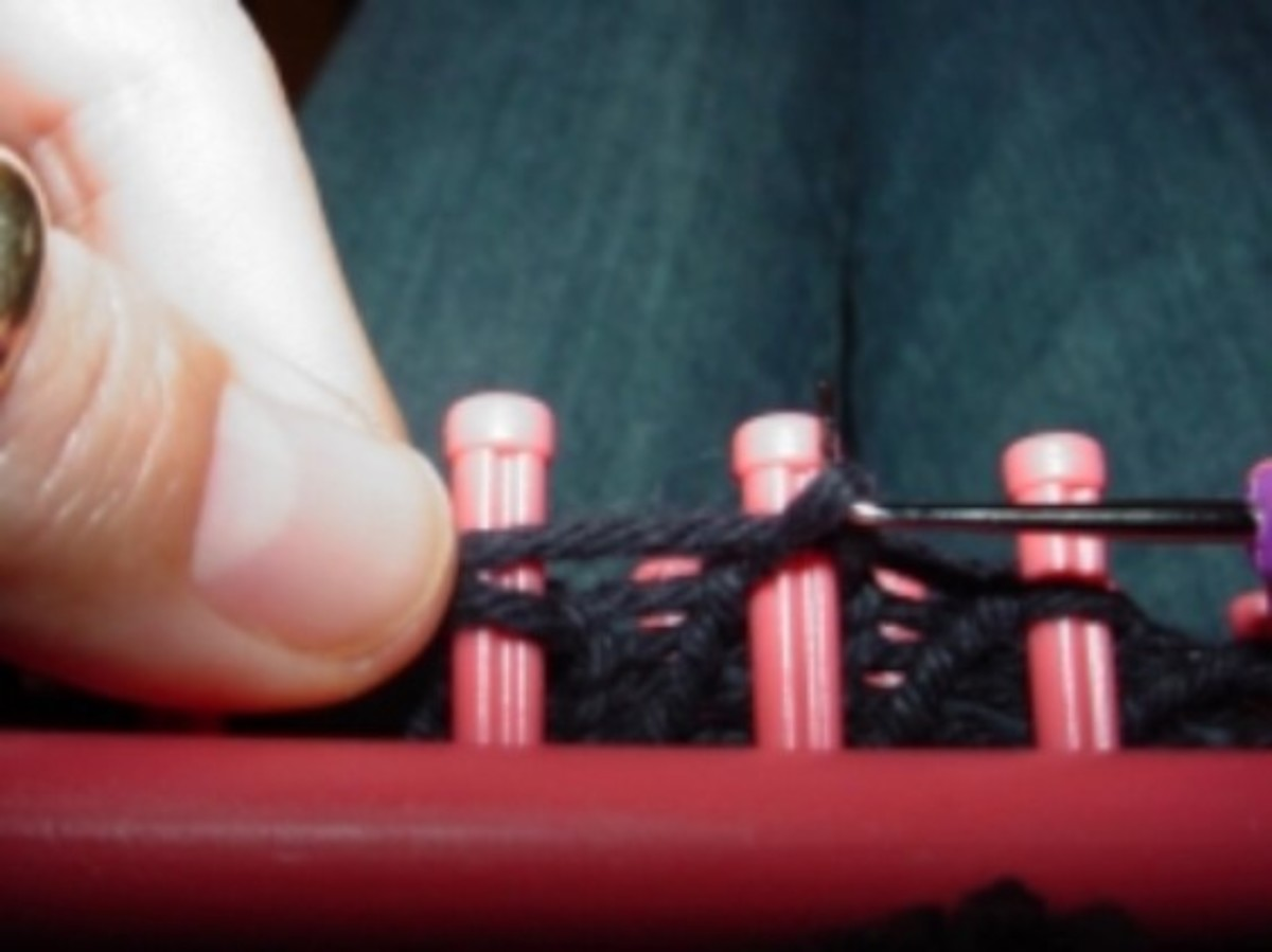 Knitting off no-wrap stitch on a Knitfy Knitter loom. This is a photo of the no-wrap stitch in progress. In the picture, the hook is being used to knit off the pink loom, as the yarn is stretched just above it across the peg. I hold the working yarn.