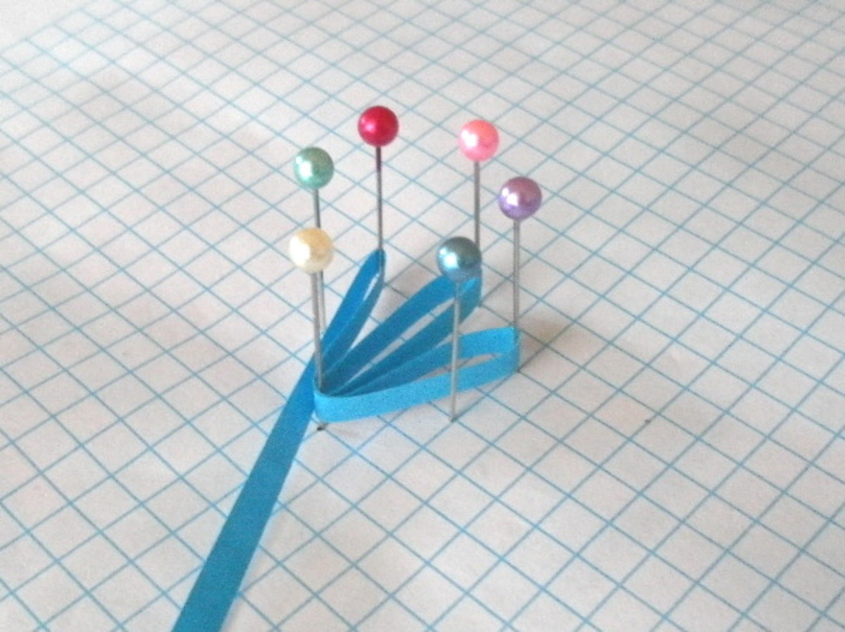 Arrange six pins in a circle and wrap a strip of paper around each pin.