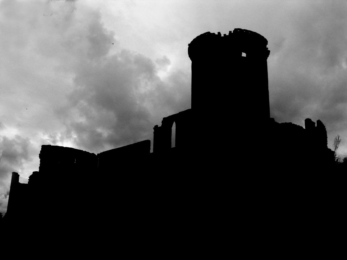 Scottish castle ruins silhouetted against a stormy sky.