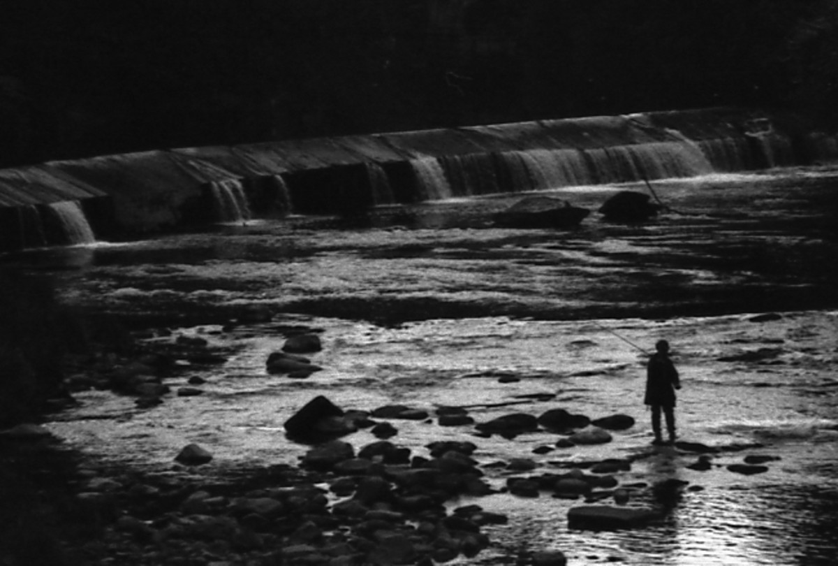 Fisherman silhouetted against reflected light from river.