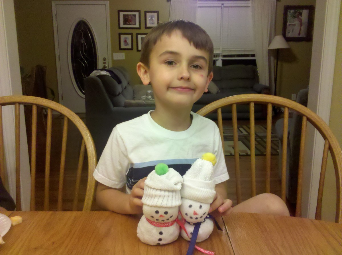 My son proudly displaying our sock snowmen!