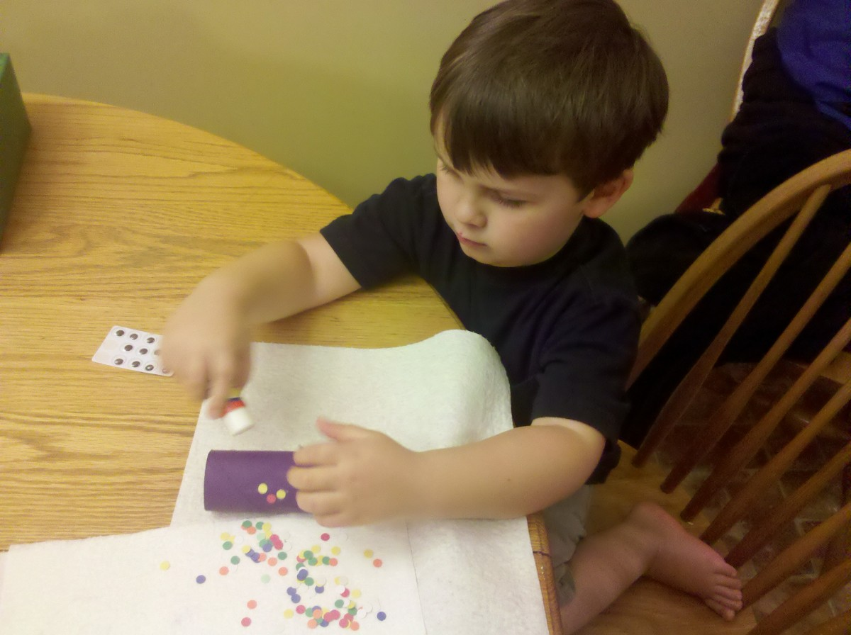 My son using a glue stick to attach the colored circles to his octopus.