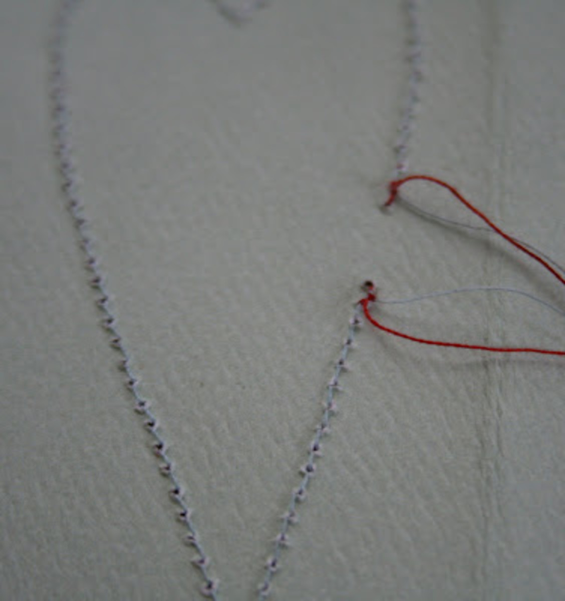Julie uses two different colors of thread for this project and then ties the threads together on the back side of her work.