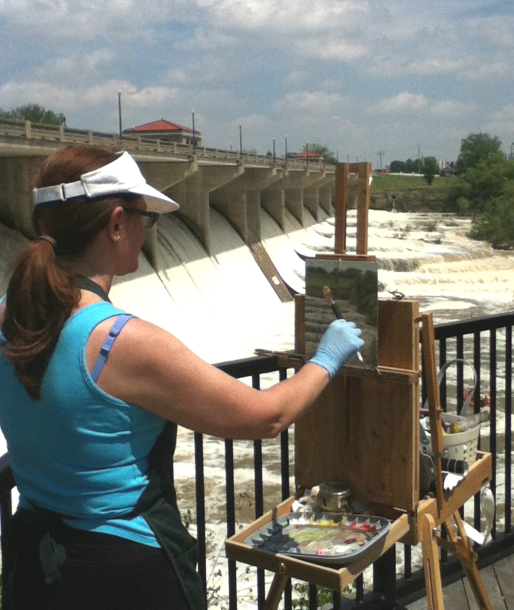 Robie Benve painting outdoors on a very sunny and hot day. Sunscreen and visor are must-haves on a day like that.