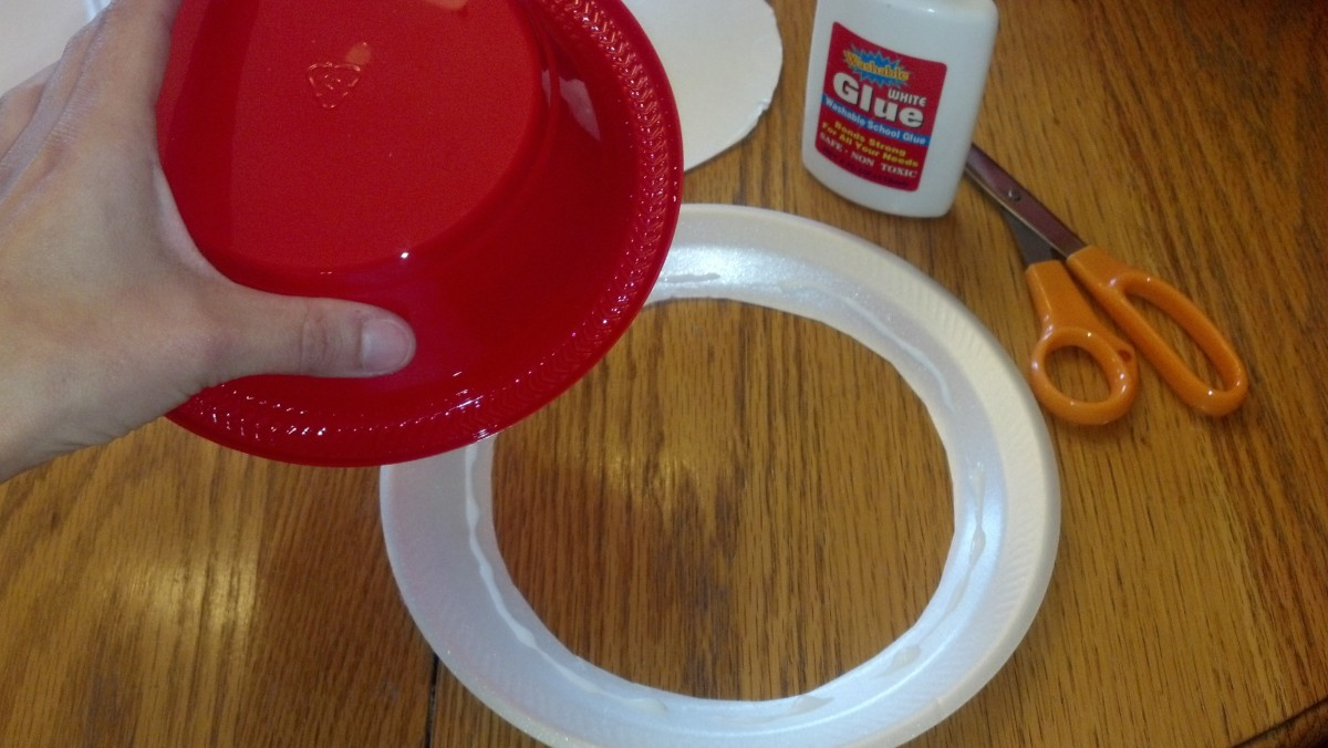 Use glue to attach bowl to ring of paper plate.
