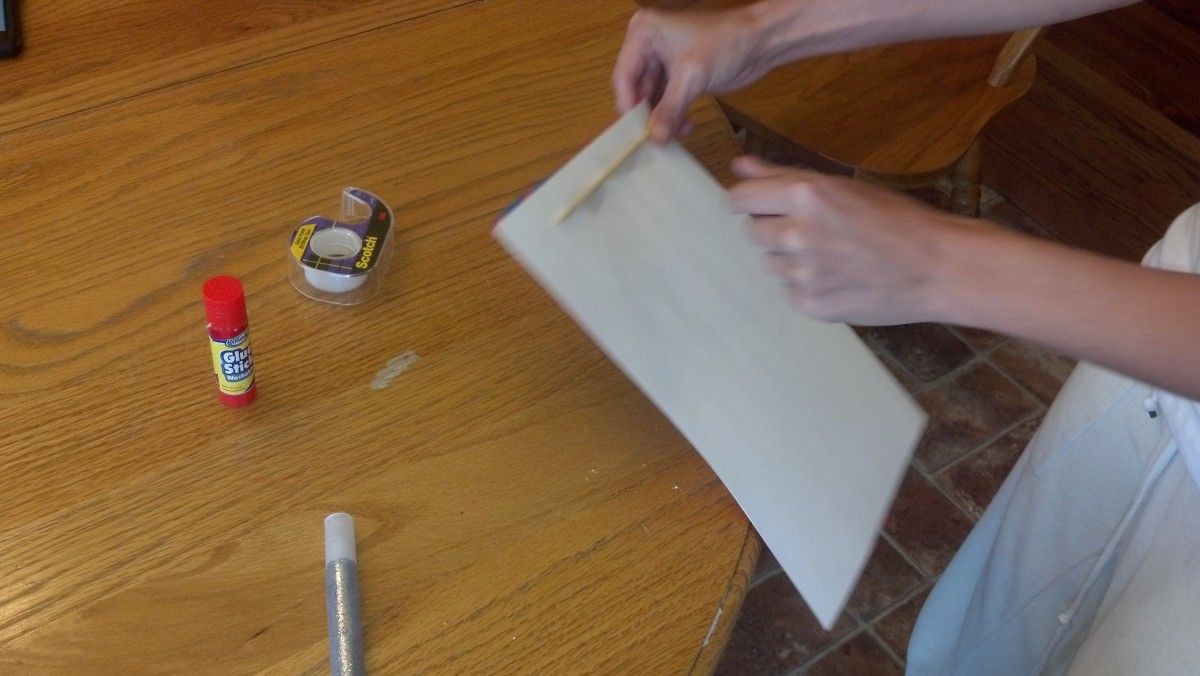 Attach a wooden stick with tape to back of flag.