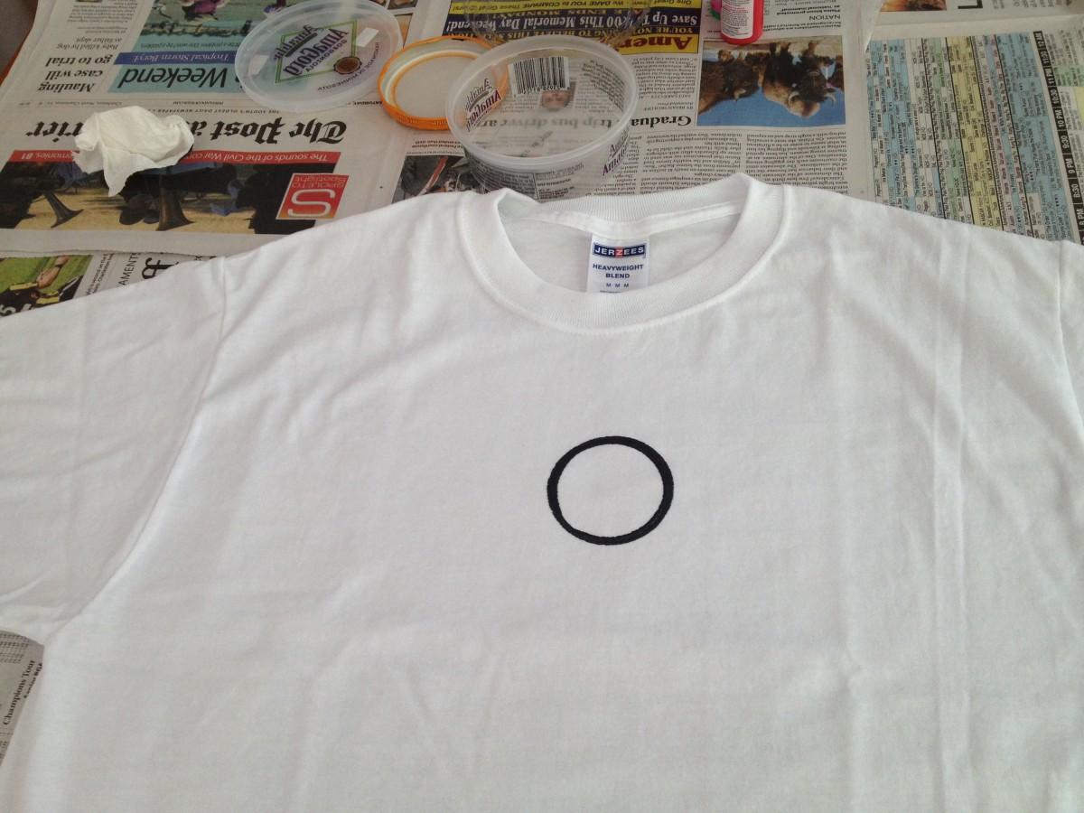 Dip top of small jar in the black paint and print first ring near the top center of the front of the t-shirt.
