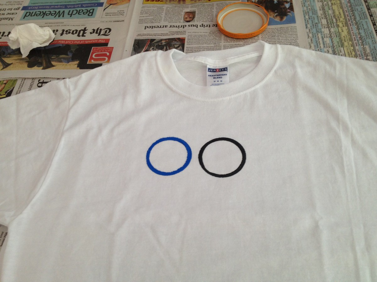 Wash and dry jar, then dip in blue paint to print the second ring 1/2 inch to the left of the black ring.