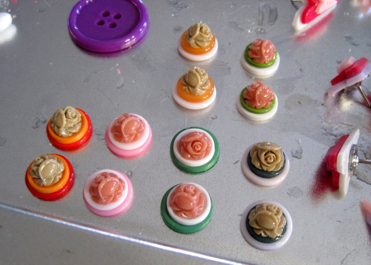 Stacked button pairs with plastic flower cabochons waiting to be made into button hair pins.