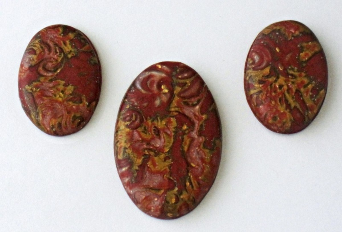 A selection of coordinating polymer clay mokume gane cabochons made from the same stack or billet